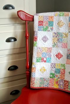"Sew Inspiring Rooms {Bitty Bits and Pieces} @ A Little Bit Biased: (Scroll down)...This quilt is a baby quilt that I made and taught a few years ago. It's a replica of an antique quilt that I bought at a local antique store call ""Star Flower Mill"" The squares are appliqued in the center of each white square. My friend Kaylene quilted an amazingly intricate design on this small quilt."