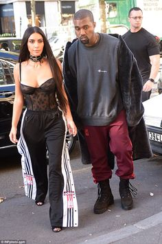 Casual couple: Kanye meanwhile, opted for a casual look in maroon tracksuit bottoms and a baggy grey sweatshirt paired with hunky lace-up boots