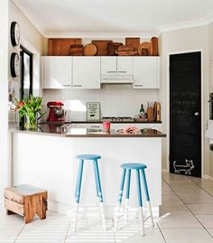 """display of cutting boards up on the top of the cabinets. A beloved collection is arranged in a random repetitive style to create a """"frieze"""" of the warm wood at the top of of the kitchen. With this kitchen in all white and looking rather plain, having that warm wood band at the top adds character and personality - Photo MAREE HORNER"""