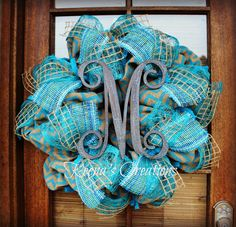 """Keena's Creations - This gorgeous wreath is truly deluxe created with natural tan  with blue chevron burlap, Turquoise banana weave ribbon, striped turquoise paper ribbon and natural window pane jute ribbon. The 10"""" """"M"""" in the center is made of Baltic birch wood hand-painted in a crackle finish with a turquoise base and a chocolate top coat. Wreath base, chevron burlap, striped paper ribbon and banana weave ribbon all purchased at http://www.trendytree.com"""