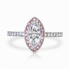 There is nothing better than having hints of your character and personality incorporated into your wedding ring. A 0.64 carat D-VVS2 marquise-cut diamond is set amidst masterful beading, perpendicularly positioned on the platinum shank that glimmers below. Fancy purplish-pink diamonds weighing 0.16 carats are pave-set around the marquise diamond, all set on 18 karat rose gold to accentuate the colors and character that radiant from of pink diamond. The shank harbors white pave-set diamonds…