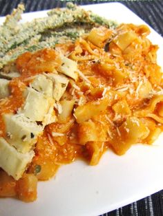 Vodka Sauce with Greek Yogurt!  1/4 cup good olive oil  1 medium yellow onion, chopped;    3 cloves of garlic, diced;    1/2 tsp crushed red pepper flakes;    1-1/2 tsp dried oregano;    1 cup vodka;    2 (28 oz) cans peeled plum tomatoes;    Kosher salt;    Freshly ground black pepper;    3/4 pound pasta;    4 Tbsp fresh oregano;    3/4 to 1 cup 2% plain Greek yogurt;    Grated Parmesan cheese