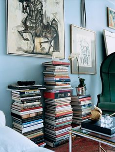 Ryan Korban. Orderly piles of orphaned books resting against the wall