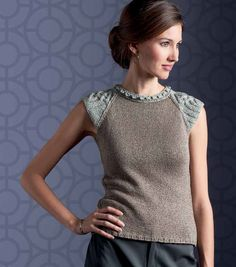 The extended shoulder sections create small sleeve caps, with Celtic designs showcased along the shoulders. The stand-up collar accentuated with bobbles and the ribbing along the sides amplifies the close-fit shaping and brings sophistication to the sl