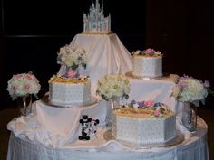 Four tier Cinderella Castle Wedding Cake with the tiers separated over different sections with plenty of lovely flowers.