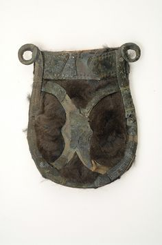 Belt pouch. Bronze, fur and paper. The bronze mountings of a belt pouch are attached to paper fastened onto squirrel fur. Grave find, Björkö, Adelsö, Uppland, Sweden.