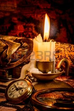 Vintage compass, pocket watch lie on an old ancient map with a lit candle Stock Photo