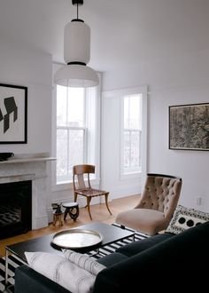 A tufted velvet chair accents the black and white color scheme. #remodelista #interiordesign #modern #blackandwhite
