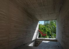 Concrete tunnel extends through a stone wall at Leyva 506 house by ATP
