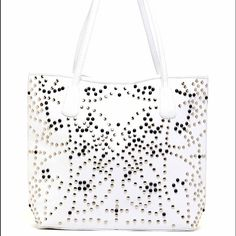 RAJ IMPORTED WHITE LEATHER STUDDED TOTE GREAT SUMMER BAG. PERFECT WITH ALL THE BRIGHT COLORS OF SPRING. STUDS VARY FROM A MUTED SILVER TO A DARKER PEWTER. WHAT I LIJE IS THE DOUBLE HANDLE STRAP DROP IS CLOSE TO 11 INCHES SO IT HANGS EASILY FROM YOUR SHOULDER AS YOU MAY STROLL THROUGH AN OUTDOOR MARKETPLACE. FLAT BOTTOM IS 4 INCHES WIDE . APPROXIMATELY 16 INCHES ACROSS AND 13 INCHES HIGH. REAL LEATHER. CLOSE UP PHOTO SHOW NATURAL VARIATION. RAJ Bags Totes