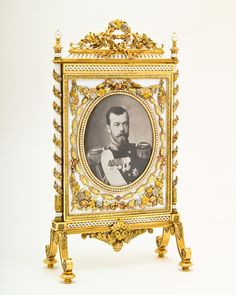 Faberge firescreen. This is a superb example of the goldsmith's art. It was created by Henrik Wigström around 1910. One side contains a photograph of Emperor Nicholas II and the other of his Empress, Alexandra Feodorovna.  The gold and platinum frame is enamelled white and seed pearls are set round the oval bezels. The whole is embellished with floral swags in multi-coloured gold. It is a stunning piece.