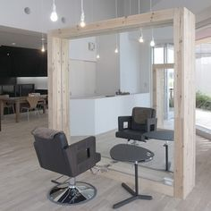 Customers sit at large wooden frames in this hair salon by Japanese studio Three.Ball.Cascade in Chiba, Japan.