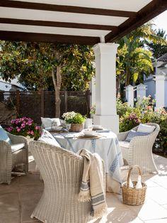 mesa puesta bajo un porche con mobiliario de mimbre blanco_00428062 O