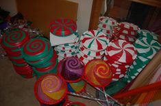 "These are my version of the ""paper plate mints"" that I saw online. I want to use them outside so I used red, green and white plastic party plates instead. The lollipops are built around existing snowflake lights that we had. I just decorated the inside of some clean plastic bowls with swirls of colored cellophane and plastic table cloths."