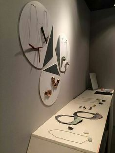 Sieraad 2014 - wall display appears to point to each other. Dark part looks like an arrow. Pieces on table are very flat.