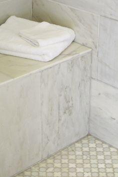 Shower with marble tiles shower surround, marble shower bench and quatrefoil tile shower floor.
