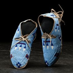 Gros Ventre/ Assiniboine Beaded Hide Moccasins thread and sinew-sewn; fully beaded with a light blue background and rose, white, and dark blue detailing; fringe decorates heel; collection number inked in sole, length 7.25 in. late 19th century Price Realized Including Buyer's Premium $1,440 04/08/2016