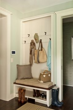 Sherwin Williams Comfort Gray Southern Living  Fabulous mudroom features gray green paint color on walls as well as hooks on built-in coat rack accented with paneling above built-in bench dressed in mushroom linen tufted cushion and built-in shoe shelf right below bench.