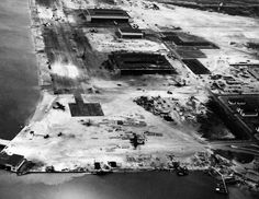 """80-G-32943: Naval Air Station Kaneohe Bay, Oahu, T.H. Aerial view of the hangar area, 9 December 1941, two days after the Japanese air attack destroyed nearly all of the station's patrol planes. Note wrecked hangar in center. There are at least six PBY """"Catalina"""" flying boats on the ramp and around the hangars."""