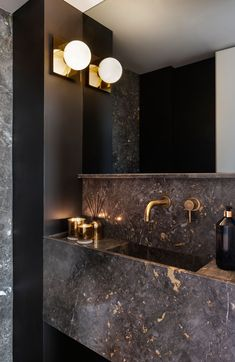 unique home accents Metallic And Black Accents Help Give This Apartment A Glamorous Interior In this modern powder room, metallic accents have been paired with dark stone and black walls for a bold and dramatic appearance. Dark Bathrooms, Modern Bathroom, Bathroom Black, Black Bath, Minimal Bathroom, Stone Bathroom, Boho Bathroom, Small Bathroom, Master Bathroom