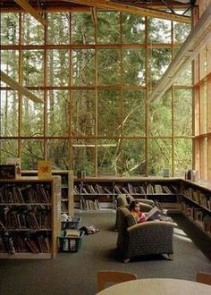 This room...the windows with nature in plain view, and tons of books, a cozy chair...just need a cup of coffee and fuzzy blanket and I'd be there all day!