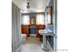 Large bungalow bath with wood built-ins and Schoolhouse Lighting