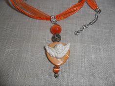 """Collier réalisé à partir d'une perle plate et d'un ange en résine, de deux perles de verre type """"oeil de chat""""."""