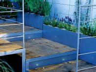 This sleek garden staircase design is constructed with an aluminum frame and wooden decking treads. This combination works well in  a garden with a contemporary look.