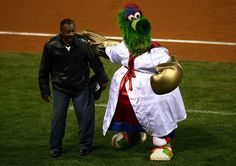 The Philly Phanatic, mascot of the Philadelphia Phillies performs with an assist from Former heavy weight champion Joe Frazier (L) against the New York Yankees in Game Four of the 2009 MLB World Series at Citizens Bank Park on November 1, 2009 in Philadelphia, Pennsylvania.