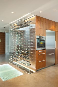 An impressive wine cooler displays bottles horizontally over steel and walnut, spanning from floor to ceiling.