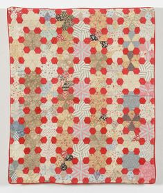 Maker:Pinney (Bartholomew), Mahala. Date:1875 - 1899.  A cotton quilt made from multi-coloured printed cotton rosettes of 5-sided jewel shapes surrounded by plain red hexagons. The quilt is hand pieced over papers and the printed cottons and shirt fabrics date from the late 19th century.  58cm x 70cm