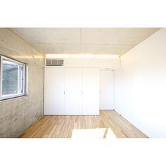 床はナラ材のフローリング。壁や天井のコンクリートの質感が、壁面・クローゼットの白と共にミニマルな空間を生み出している。