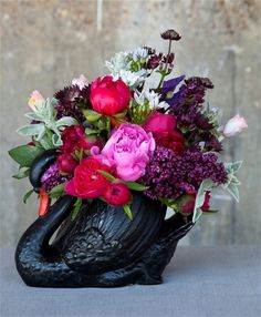 Vic Brotherson, founder of Scarlet    & Violet , based in Kensal Rise, London, loves British flowers,    particularly peonies. This vintage black swan vase is home to a stunning low    arrangement of early British peonies, astrantia, stachys, lilac, alliums,    poppies and clematis.