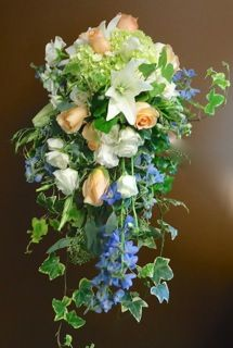 Cascade bouquet of soft pastel colors with hydrangea, delphinium, lilies and roses.