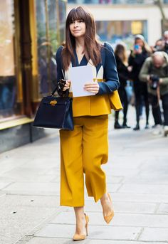 A navy and yellow jacket is worn with matching yellow trousers, suede yellow heels, and a navy leather handbag
