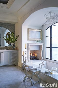 """The arched window and the view from this California bathroom were so magnificent designer Ohara Davies-Gaetano didn't want to put a big white porcelain tub in front of it. Instead, she designed a sunken bath made from slabs of Crema Marfil marble. """"Imagine lying in the bath with the flames flickering and the sun setting over the Pacific,"""" she says. """"What could be more relaxing?"""" - HouseBeautiful.com"""