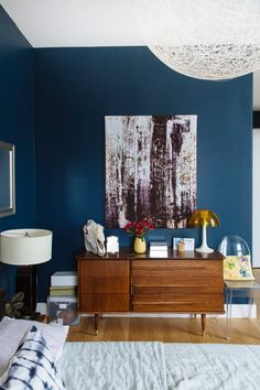 Our Favorite Bedrooms : Bedroom with a dark blue wall, mid century dresser, and a string sphere light