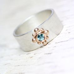 A modern wide wedding band in silver featuring an ornamental detail in 14k rose gold. Eisrose (ice rose) has a sparkly 3mm blue zircon set in the center. The color combination of the white silver, warm rose gold and chilled blue is heavenly. A comfortable unisex wedding ring that can also be made with other gemstones.  Ring width: 8mm Ring thickness: 1.2mm  Shown in size 7.5 * Made to order in your size (please allow 1-2 weeks for production) nangijalajewelry.etsy.com