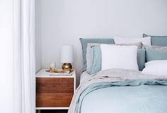 Restful bedroom with contemporary two-tone nightstand topped with a gold wishbone paperweight and small round gold lamp beside the bed layered with blue, gray and white bed linens.