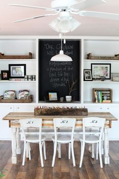 Dining room white table white chairs chalkboard