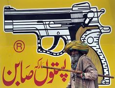 A pedestrian walks by a mural of a handgun on Tuesday in the city of Multan, located in Pakistan's Punjab province. Photo by Bay Ismoyo/AFP/Getty Images.
