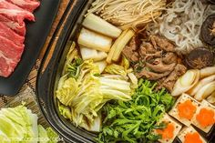 Authentic homemade Japanese sukiyaki recipe with seared marbled beef and variety of vegetables including enoki, shungiku, and napa cabbage cooked in a soy sauce broth.