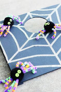 Decorate your tabletop cornhole boards with black acrylic paint, double-sided tape coated with silver glitter (for the perfect, shiny web), and any fake spiders of your choosing.