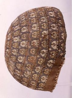 Western European, dated 1200-1400, 20 cm diameter. Held in Sint-Truiden [district], Limburg, Belgium in the Assumption Church O.L.Vrouw. The underlying net is knotted in red/beige organzizinjde (silk thread?) with  +/- 64 intersections per cm2. The embroidery over it (click through and zoom!) is in grey, white and beige organzinzijde in stopwerk (knotted stitch? Sorry, rubbish at Dutch) over the mesh. Woven cords form loops at edge for tightening cord.