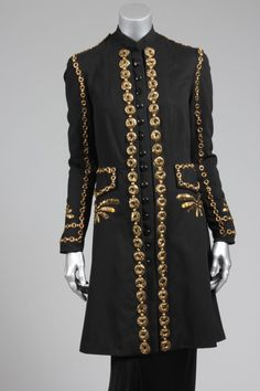 Elsa Schiaparelli couture embroidered 'Persian Prince' black wool evening coat, Autumn-Winter, 1937-8, labelled `Schiaparelli London' and numbered 5521, the front closure, pockets and sleeves adorned with gilt strip rosettes and square brass beads gold strip palmettes embroidered below the pockets and to the cuffs, stand collar, lined in black silk crepe