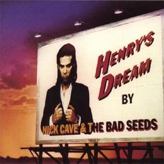 Nick Cave: 'Henry's Dream' -   Designed by the ever cool Anton Corbijn, his cover for Cave's Henry's Dream captures the essence of Cave. It's moody, dark and gothic. Check the colours of the sky and the imposing billboard featuring a suitably serious Cave. In a word, evocative!