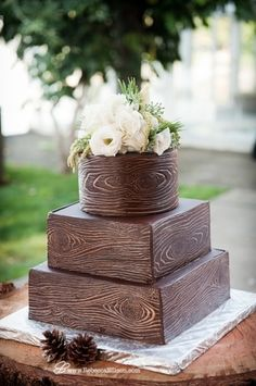 A chocolate wedding cake with a rustic woodcut design, pinecone decorations and white floral cake toppers. | ARIA | STYLE in Seattle, Washington