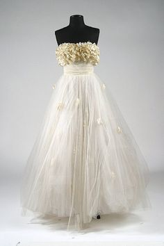 This beautiful dress, designed by Edith Head for Elizabeth Taylor to wear in 1951's, A PLACE IN THE SUN. A strapless boned bodice top with an enormous white tulle skirt over pale green satin, and white violets covering the bust. One could argue that this dress defined a look for proms and brides for the following decade.