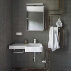 Decorative exposed pipe in gray bathroom