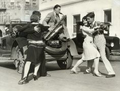 """When Myriads of dancers commenced practicing thru Los Angeles' streets, they stopped traffic in many quarters as motorists stared in amazement. This photo shows two couples, accompanied by their trainer-musician, """"working out"""" on the streets for the coming marathon. Left to right; Erdene Smith, Tom Grana and Marion Joyce and john Grana. © Underwood & Underwood/Corbis, March 10, 1927 [stock photo id: VV922]"""